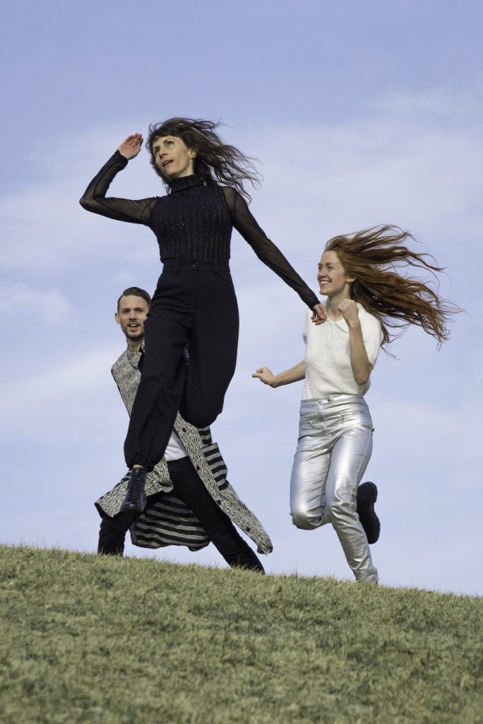 Molly Heller and two other dancers leap and move on a grassy hill.