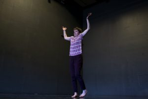 Molly Rose Williams, dressed in a striped t-shirt, holds her hands above her head.